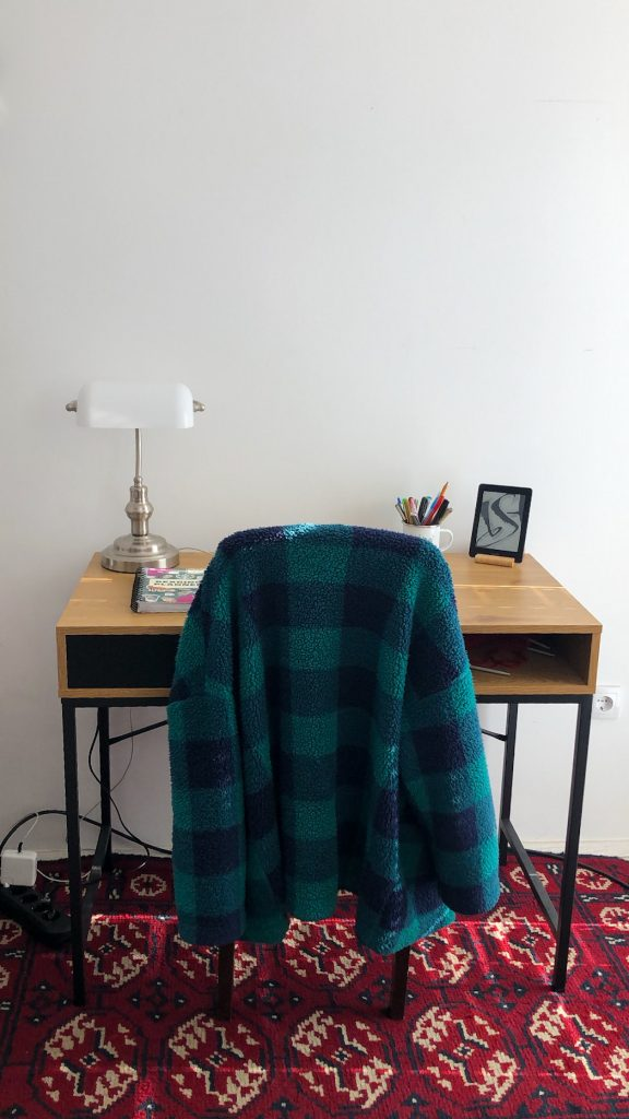A picture of wooden desk on the red bokhara oriental rug. Green checkered cardigan is draped over the chair. On the desk there is white banker's lamp, Kindle, journal and cup with pens.